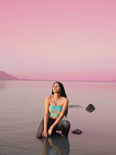Full length of woman relaxing on beach against sky during sunset