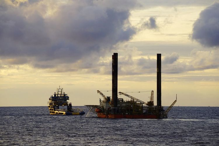 A silhoutte of an offshore vessel AHTS towing an oil platform at sea Sea Ahts Oil Platform Oil Rig Jackup Rig Ship Towing Ocean Sunset Oil And Gas Industrial Economy