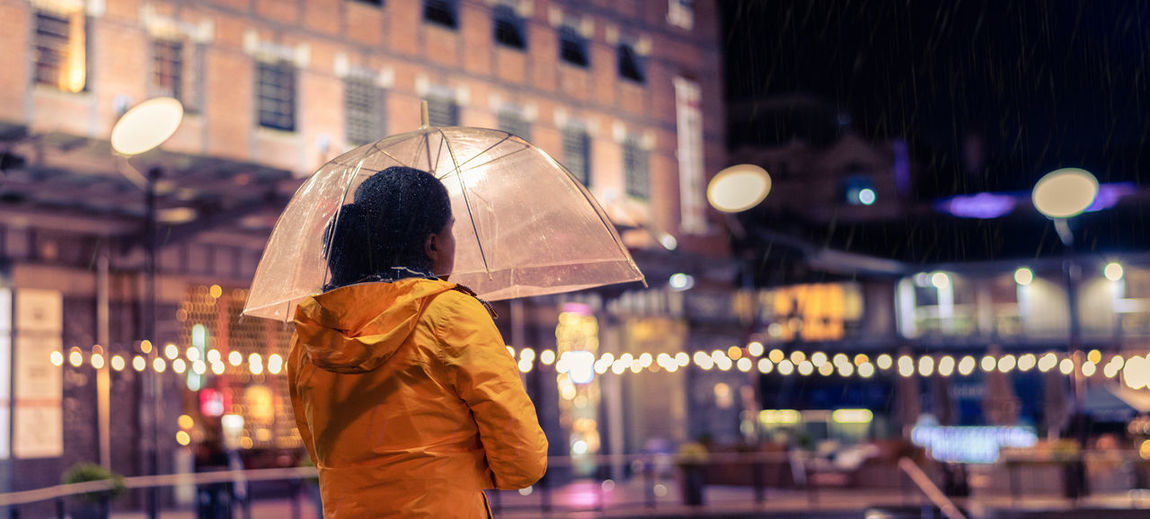 Rear View Of Woman Standing With Umbrella In City At Night
