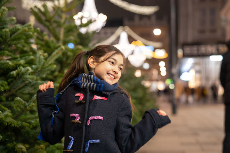 Cute smiling girl looking away on street