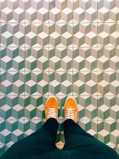 Woman in orange shoes standing on tiled floor