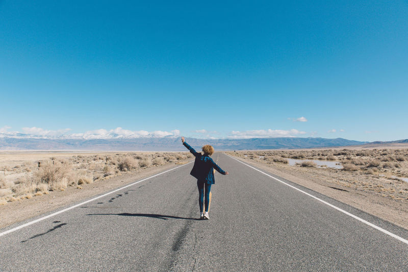 Woman standing on road against clear sky