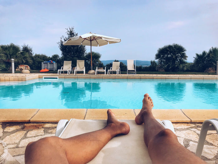 Low section of man relaxing against swimming pool
