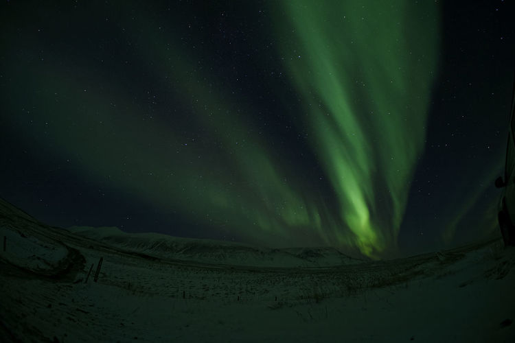 Scenic view of snowcapped landscape against sky with northern lights shinig