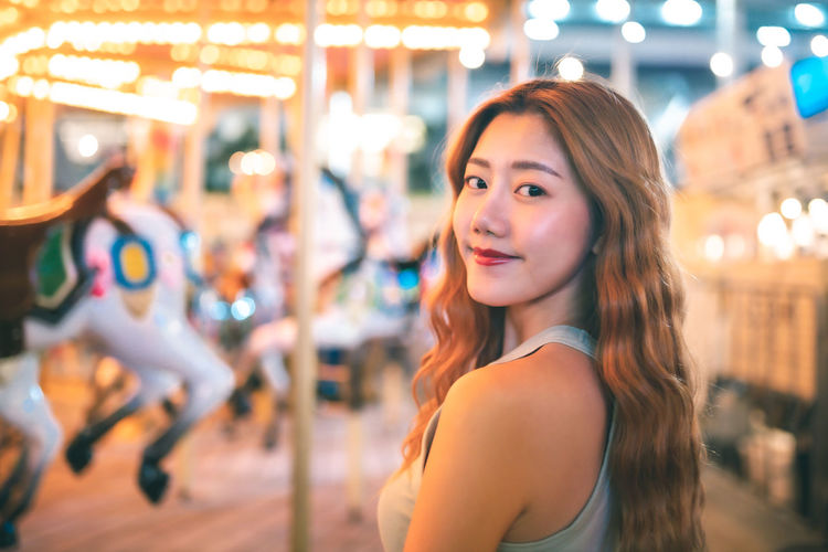Portrait of smiling young woman at night