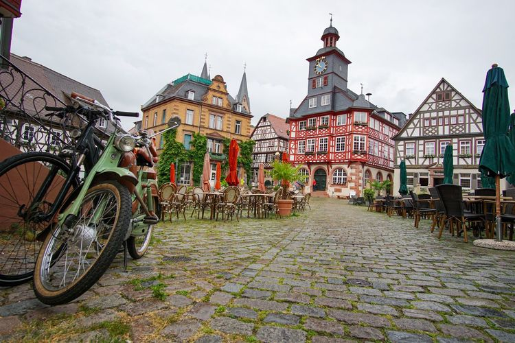 Bicycles parked on street amidst buildings in city