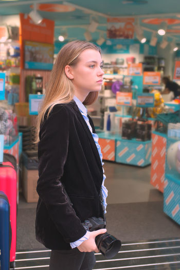 Side view of young woman looking away while standing at home