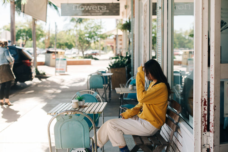 Side view of woman sitting at sidewalk cafe