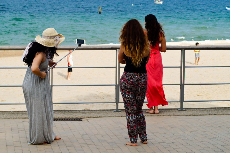 Full length of woman with friends taking selfie at beach