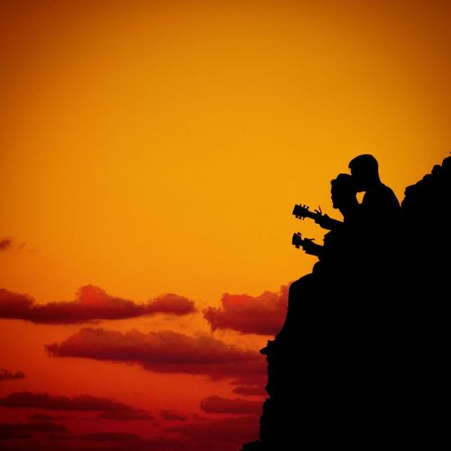 Silhouette Of Men At Sunset