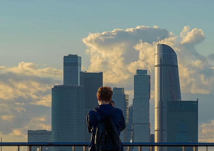 Rear view of man looking at modern buildings in city against cloudy sky