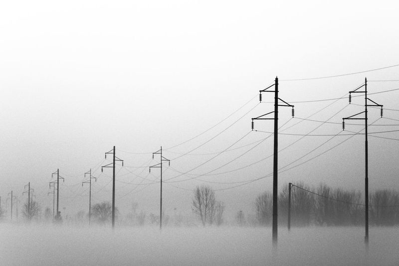 Cable Cold Temperature Cold Weather Connection Early Morning Electricity  Electricity Pylon Electricity Tower Environmental Conservation Fading Fog Fuel And Power Generation Low Angle View Metal Mist Monochrome No People Outdoors Poles Power Cable Power Line  Power Supply Sky Technology The Way Forward