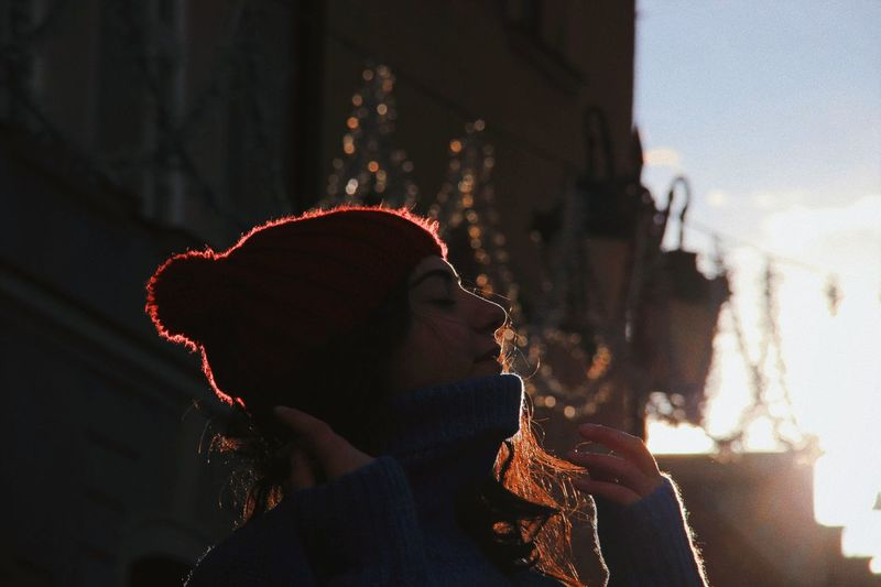 Low angle view of young woman with eyes closed against sky