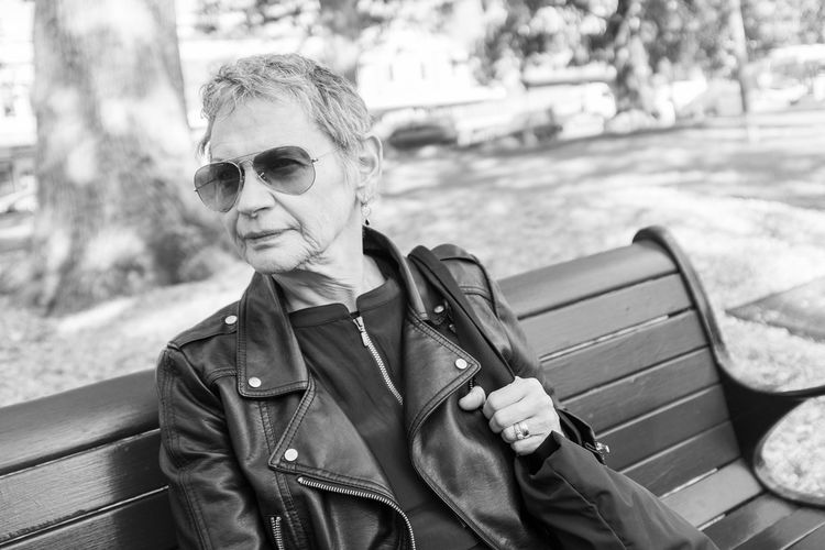 Senior woman in black jacket Adult Black And White Casual Clothing Clothing Day Fashion Focus On Foreground Front View Glasses Jacket Leather Leisure Activity Lifestyles One Person Outdoors Portrait Real People Scarf Sunglasses Waist Up Warm Clothing Women