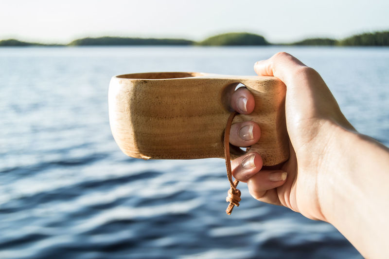Fresh cup of coffee Coffee Cup Coffee Kuksa Summer Lakeside Bluewater Object Photography Hanging Out Hand EyeEm Selects Human Hand Water Lake Summer Holding Drink Portrait Close-up Sky Personal Perspective Beverage Archipelago