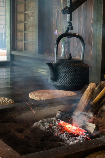 Close-up of teapot hanging over fire