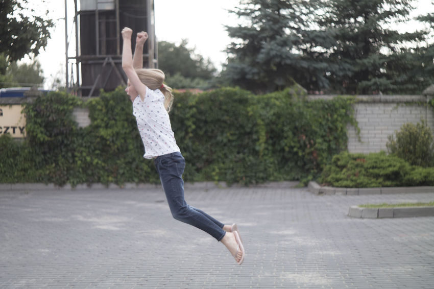 A collection of photos of a jumping girl on a car park in front of the school Blond Car Park Casual Clothing Childhood Children Enjoy Freedom Girl Joy Jump Lifestyles Long Legs Outdoors Person Showing Imperfection The Color Of School