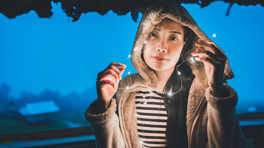Portrait of woman holding illuminated string lights at night