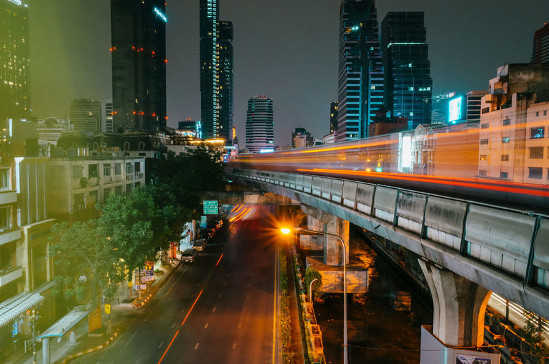 Backlights of moving cars and a blurred passing skytrain with the skyline of Bangkok in the background Built Structure Architecture Illuminated Building Exterior City Transportation Motion Night Street No People Mode Of Transportation Building City Life Connection Rail Transportation Office Building Exterior Long Exposure Public Transportation Bridge Nature Bridge - Man Made Structure Skyscraper Cityscape Bangkok Skytrain