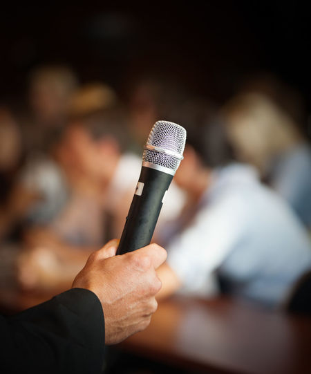 Cropped hand of male public speaker holding microphone in lecture hall