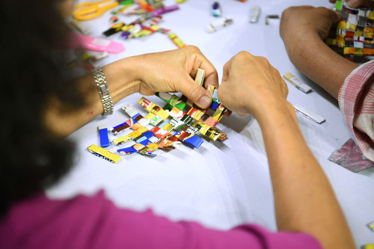 Cropped hands of woman making paper craft at home