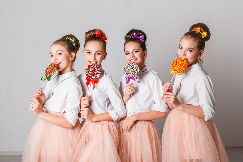 Beautiful teenage girls in pink tutu or tulle skirts with colorful lollipops in studio on white background Advertising Beautiful Beautuful Bows Fashion Fun Makeup Models Pink Stylish Cute Hairstyle Indoors  People Smiling Sweets Teenage Girls Twins