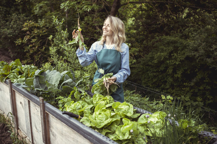 Woman standing in front of plants
