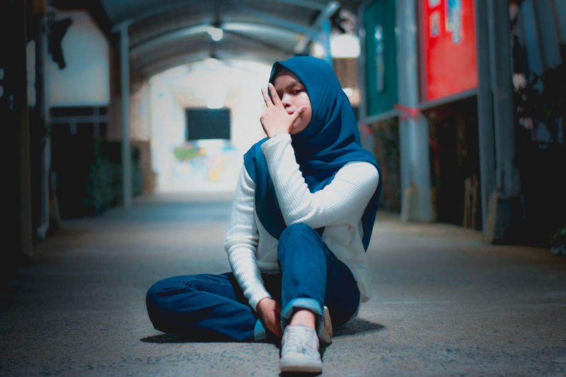 Portrait of young woman wearing hijab sitting outdoors at night