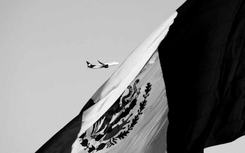 Low Angle View Of Mexican Flag Against Airplane And Sky On Sunny Day