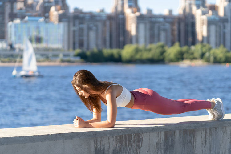 Full length of woman exercising by river against cityscape