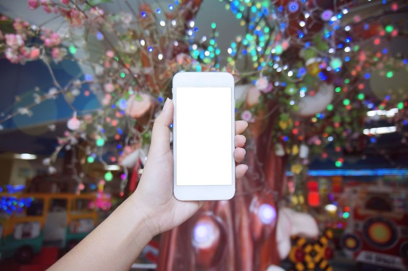 Cropped Hand Of Woman Holding Mobile Phone Against Illuminated Decoration