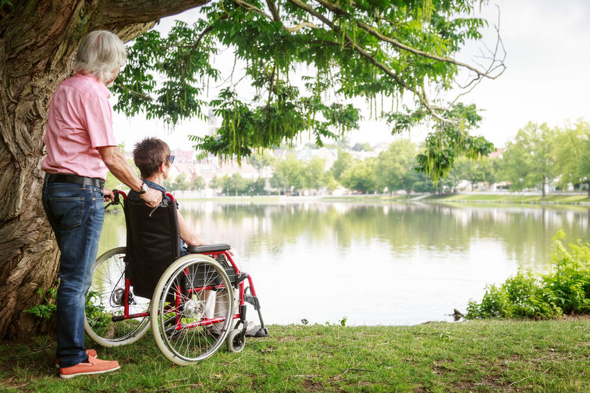Care Caretaker Fun Happy Nature Active Lifestyle  Active Seniors Differing Abilities Lifestyles Married Couple Men Old Age Outdoors Park People Retirement Senior Senior Adult Senior Men Senior Women Summer Two People Wheelchair Women