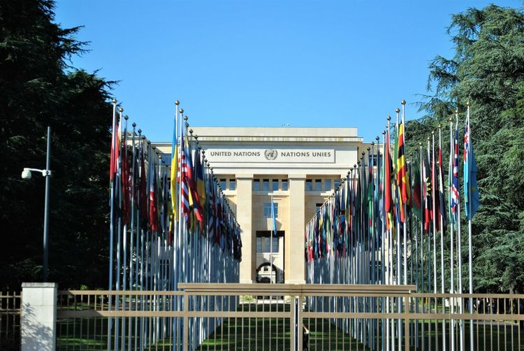 Flags outside united nations office at geneva against clear sky