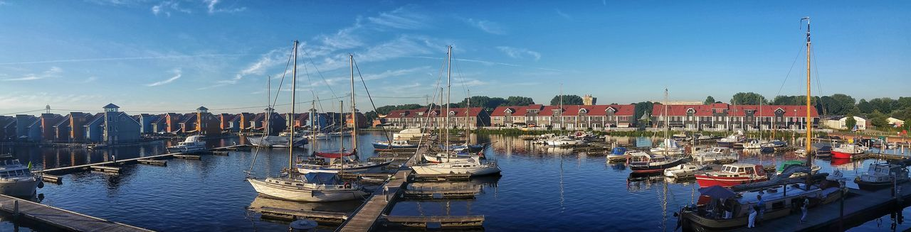 Panoramic view of boats moored at harbor by buildings against sky