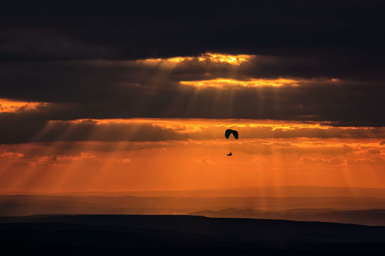A lonely paraglider in the awesome light of the sunset, a grand landscape in Romania Dramatic Sky Romania Sunrays Adventure Beauty In Nature Cloud - Sky Dramatic Sunset Dusk Extreme Sports Flying Landscape Light And Shadow Nature One Person Outdoors Parachute Paragliding Real People Scenics Silhouette Sky Sunset Go Higher EyeEmNewHere