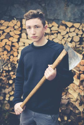 Portrait of teenage boy cutting log