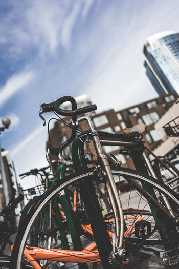 Close-up of bicycle parked against sky in city