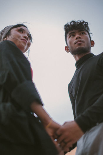 Low angle view of couple standing against sky