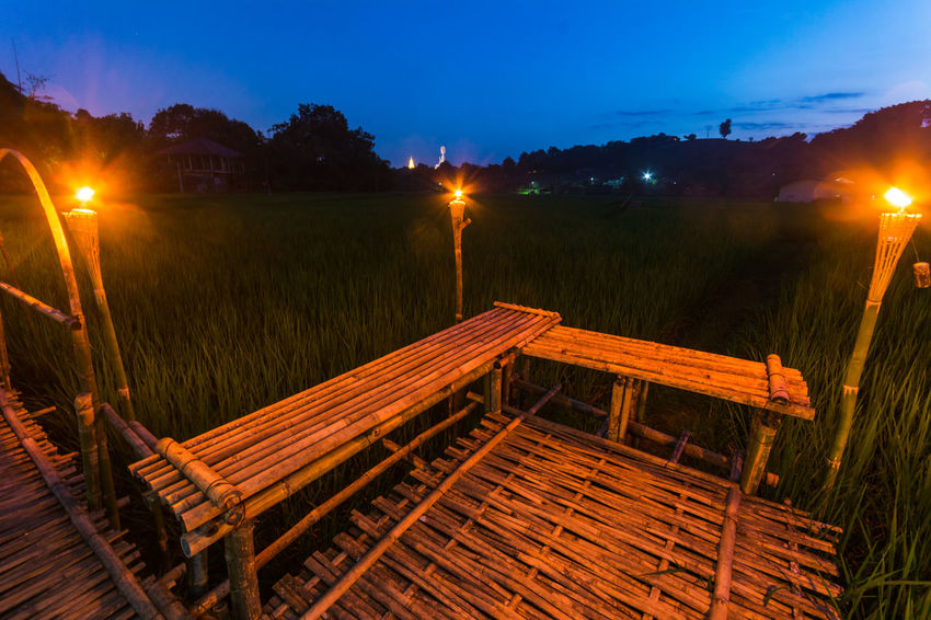 Bamboo Bridge in Paddy Field, Chiang Rai, Thailand. Absence Bamboo Bridge Bamboo Bridge In Paddy Field, Chiang Rai, Thailand. Bench Blue Boardwalk Cottage Dusk Empty Illuminated Night No People Outdoors Paddy Field Plank Relaxation Scenics Sky Solitude Street Light Tranquil Scene Tranquility Wood Wood - Material Wooden