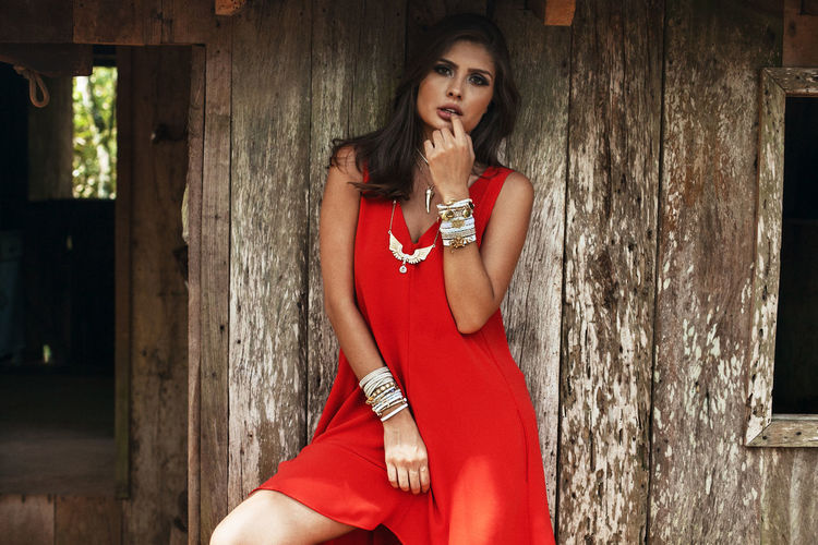 Seducing woman in red dress standing at abandoned house
