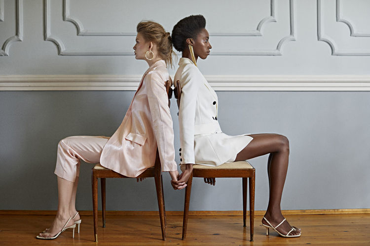 Side view of women holding hands while sitting on chair against wall