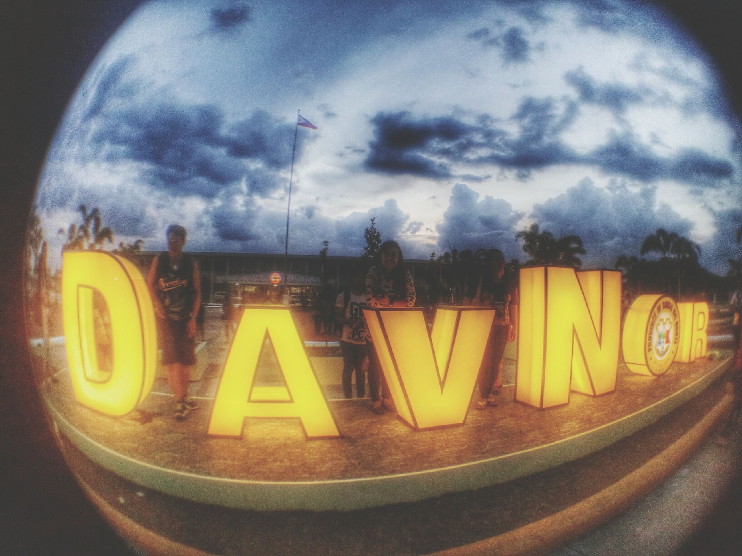 sky, text, yellow, communication, western script, cloud - sky, transportation, illuminated, cloudy, circle, road sign, cloud, no people, capital letter, outdoors, close-up, information sign, night, low angle view, glass - material