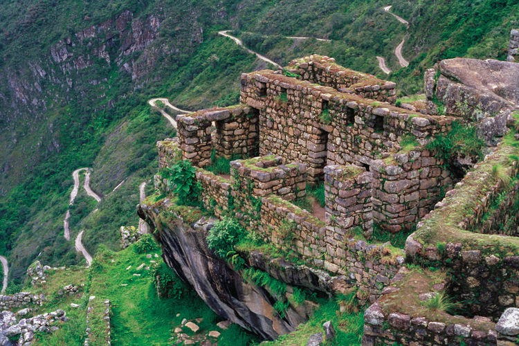 Stone walls from houses and road in the ancient inca city of machu picchu, in peru.