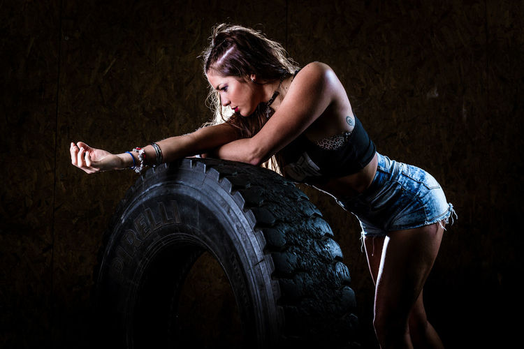 Side view of woman standing by tire at gym