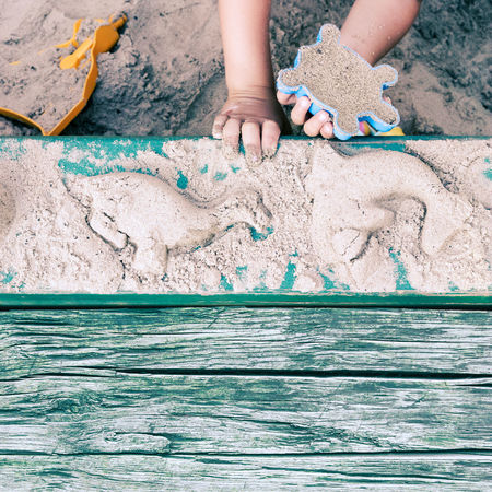 Kid creating animal forms with sand Adorable Animal Child Childhood Copy Space Day Dinosaur Dolphin Enjoy Hand Kid Mold Outdoors Playground Playing Sand Sandpit Season  Shape Shell Summer Summertime Sunset Toddler  Toy