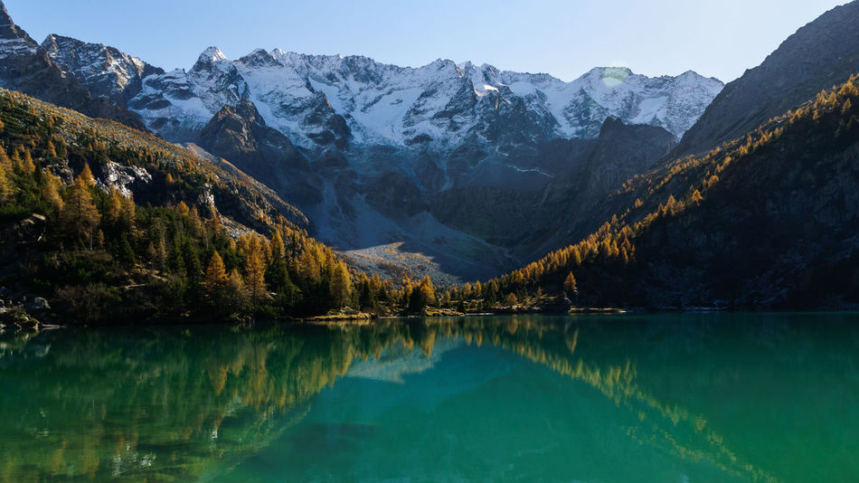 Beauty In Nature Blue Lake Forest Hiking Lake Landscape Mountain Mountain Lake Mountain Peak Mountain Range Nature Outdoors Pine Woodland Reflection Reflection Scenics Snow Sunny Day Tree Water Water Reflections
