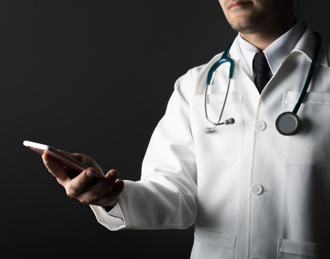 Midsection Of Doctor Holding Smart Phone Over Black Background