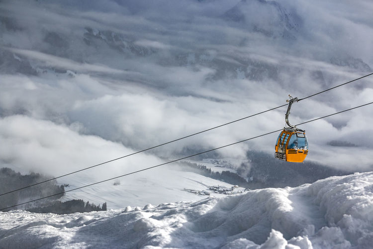 Overhead cable car over snowcapped mountains against sky