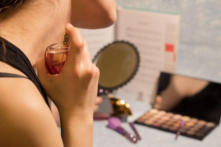 Midsection of woman applying perfume on neck during sunny day