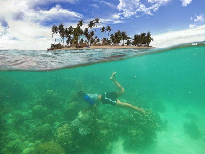 Man swimming undersea against sky